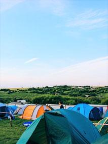 Mit der Camping-Versicherung der ERGO Reiseversicherung auf der sicheren Seite: viele bunte Zelte unter blauem Himmel auf einem Campingplatz