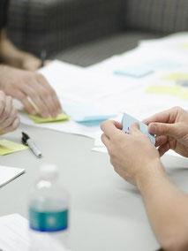 Mit der Seminarversicherung der ERGO Reiseversicherung auf der sicheren Seite: bunte Stifte und Zettel in Menschenhänden bei einem Seminar oder Workshop