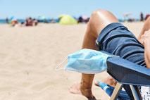 Mann im Liegestuhl am Meer mit Maske im Urlaub mit Corona-Reiseschutz