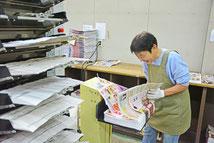 【写真】折込広告を新聞にセットしているところ