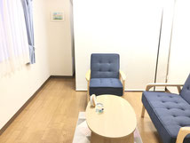 出窓と青いソファーのある一室です。