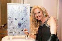 Viktoria Herrmann unterzeichnet die zu versteigernde Heizung © ExperiArts Entertainment - Thomas Ix