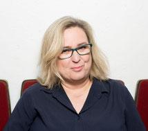 Foto von Anne Bax bei einer Lesung (mit Mikrofon und Lesebrille)