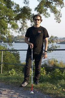 Erdin steht auf dem Rasen, Blick zur Kamera und einen Blindenstock in der rechten Hand. Schwarz gekleidet. Im Hintergrund Bäume und das Elbwasser
