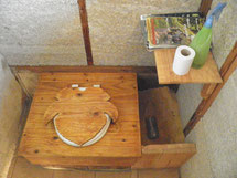 un toilette avec des copeaux de bois (à droite) pour couvrir
