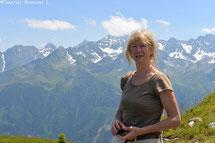 Une femme blonde en tee shirt avec une montagne en fond, ambiance ensoleillée