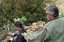 un homme debout fait un geste vers une fille qui a dans sa main une boite. En fond cactus, arbres et cailloux