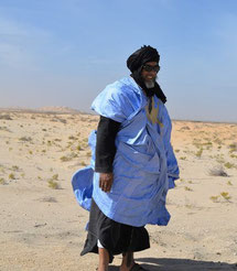 Un homme Mauritanien en habit traditionnel boubou bleu et cheche noir sur la tête, avec le désert en fond