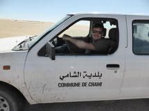"""Un homme, au volant d'une voiture où il est écrit """"commune de Chami"""" en Français et en Arabe"""