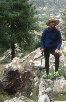 Un homme avec un chapeau coloré et des baskets, la montagne en fond