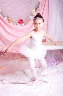Fotoshooting bei Vivaladanse in der Ballettschule. Zu sehen eine junge Ballettschülerin in einer märchenhaften rosa-weißen Kulisse, die gerade eine Ballettfigur macht.