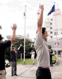 北上市の旗を掲揚後、万歳する漢那副市長(中央左)と職員ら=28日午前石垣市役所