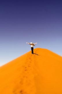 rote Sandduene  vor blauem Himmel, Person mit ausgestreckten Armen am Gipfel - Schmerzbewältigung  © Bethel Fath