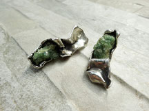 Deux grosses boucles d'oreilles avec deux grosses pierres à cristaux verts sont posées sur un fond gris.
