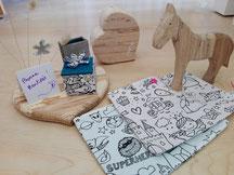 des pochettes, un cheval en bois de 15cm de hauteur, un coeur en bois à poser, une boite en papier