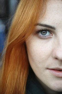 senkrechtes halbes Profilbild einer rothaarigen, schönen Frau