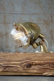 vintage bodenlampe aus einem altholzbalken und einer schifflampe in gold und led