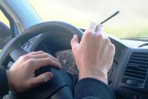 Hände am Steuerrad beim Auto fahren mit CBD Joint in der Hand