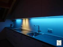 farbwechselnde RGB Nischbenrückwandbeleuchtung in blau Küche in Dachschräge angepasst, RGB Beleuchtung in Aluminiumschiene flächenbündig im Oberschrank Dachküche eingelassen, Maßküche in Dachschräge weiß mit RGB-Nischenrückwandbeleuchtung