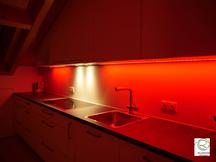 farbwechselnde RGB Nischbenrückwandbeleuchtung in rot Küche in Dachschräge angepasst, RGB Beleuchtung in Aluminiumschiene flächenbündig im Oberschrank Dachküche eingelassen, Maßküche in Dachschräge weiß mit RGB-Nischenrückwandbeleuchtung
