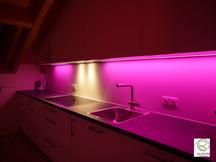 farbwechselnde RGB Nischbenrückwandbeleuchtung in pink Küche in Dachschräge angepasst, RGB Beleuchtung in Aluminiumschiene flächenbündig im Oberschrank Dachküche eingelassen, Maßküche in Dachschräge weiß mit RGB-Nischenrückwandbeleuchtung
