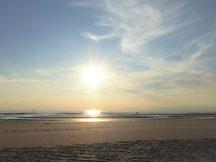brauner Strand vor untergehender Sonne, die sich im Wasser spiegelt