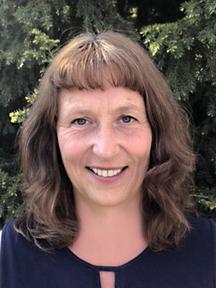 Porträt von Franziska Arni: Lächelnd, mit braunen, schulterlangen Haaren mit Stirnfransen und einer dunkelblauen Bluse. Im Hintergrund sind grüne Nadelbäume.