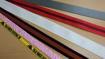 ベルトやリボンにシルク印刷、箔押し、防炎加工、撥水加工、樹脂コーティングなどの二次加工を加えた細巾織物