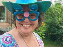 Susanne Christine Drdla mit Faschingsbrille und Faschingshut, lachend.