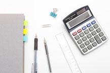 費用を算出する電卓と筆記用具と資料