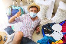 Mann mit Maske plant Urlaub und sitzt auf gepackten Koffern, gut, dass er eine Corona Covid-19 Zusatzversicherung abgeschlossen hat