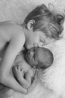 Junge hält Baby im Arm