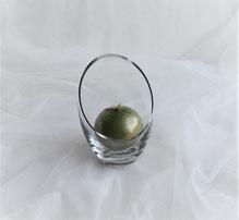 Grüne Kugelkerze im Glas