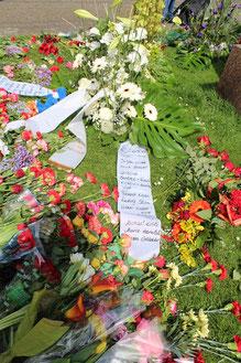Sie erinnern an die Millionen von Toten und zeichnen mit ihrem Namen auf der Schleife