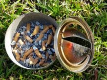 Voller Aschenbecher im Gras. Alleine der Anblick weckt den Wunsch ein stolzer Nichtraucher zu werden und zu bleiben.