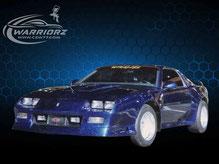 カスタムペイント、ブラックのボディーにブルーグリーンのスピンドリフト塗装された1990年カマロZ28の写真