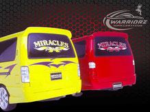 カスタムペイント車、黄色いボディーにトライバル塗装されたハイエースと赤に塗装された二台のハイエースのリヤーエンドの写真