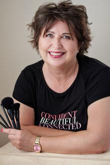 Sibylle Hübner - Selbständige Beauty Consultnt mit Mary Kay aus Frankfurt hält Schminkpinsel in der Hand und ist glücklich