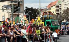 """Zuschauer am Herrmannplatz, LKW """"Wir sind Neukölln"""" biegt um die Ecke. Karneval der Kulturen. Foto: Helga Karl"""