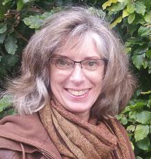 Een vrouw, Joke Zonneveld, staat met haar armen in haar zij, en lacht stralend. Ze heeft bruin haar en draagt een bril. Achter haar is een witte muur van haar Atelier De Rode Draad