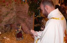5-L'enfant Jésus est déposé délicatement dans la crèche par le célébrant.