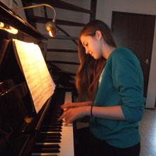 Individueller Klavierunterricht für Jugendliche   Junges Mädchen am Klavier, lächelt