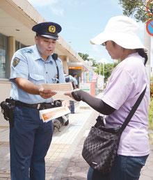 振り込め詐欺などの注意喚起のチラシを配布する警察官と受け取る市民=15日午後、八重山郵便局前