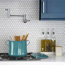 Kitchen with small white hexagon backsplash tiles, blue Shaker-style cabinets, and a teal-colored pot on the stove