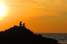Deux silhouettes assises sur un rocher surplombant la mer à la tombée de la nuit