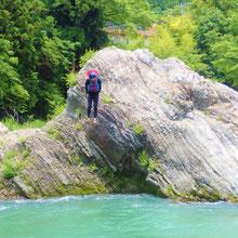 ラフティングツアーの途中、岩の上から多摩川に飛び込むゲスト