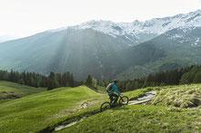 Mann fährt auf seinem neuen Riese & Müller Superdelite durch eine hügelige Landschaft