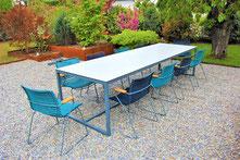 Gartentisch mit acht Stühlen in einem Garten