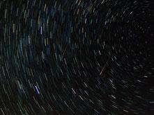 Die Erde dreht sich um ihre eigene Achse und bewegt sich zugleich auf einer weiten Bahn um die Sonne. Das veranschaulicht dieses Sternschnuppenfoto.