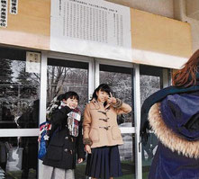 合格発表の掲示板の前で記念撮影する受験生(3月17日北海道新聞朝刊より)